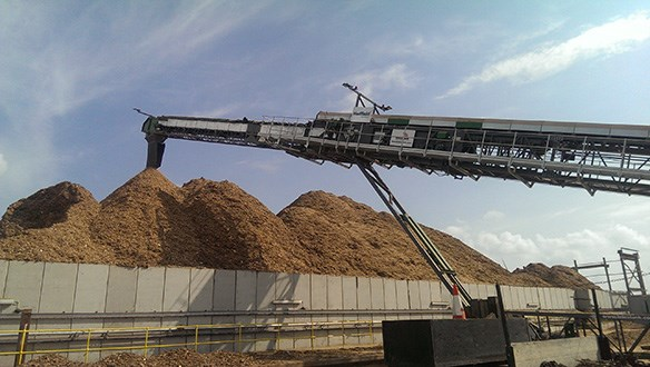 Radial conveyor stockpiling woodchips